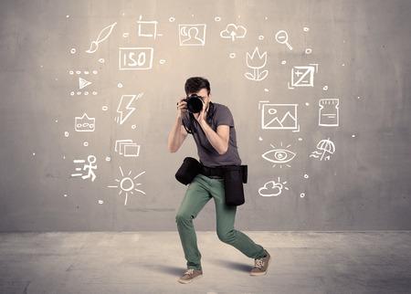 amateur: Una manía fotógrafo aprendizaje aficionado a utilizar una cámara digital profesional con ajuste de la cámara iconos en el concepto de la pared de fondo