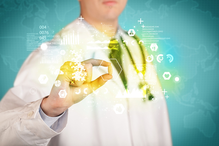 cross ties: A doctor in white coat with a stethoscope on one shoulder holding a pill with green glowing graphs, lines, numbers, charts, between his fingers Stock Photo