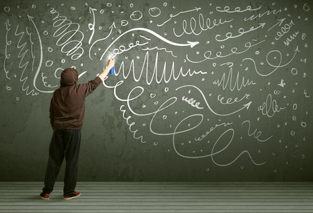urban culture: Young urban painter drawing curly lines and arrows on the wall Stock Photo