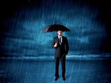 Uomo d'affari in piedi in pioggia con un concetto di ombrello sullo sfondo