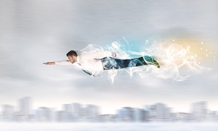 left behind: Hero super man flying above city with smoke left behind concept Stock Photo