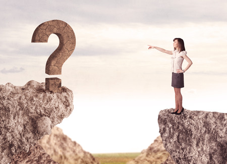 bridging the gap: Businesswoman standing on the edge of mountain with a rock question mark on the other side Stock Photo