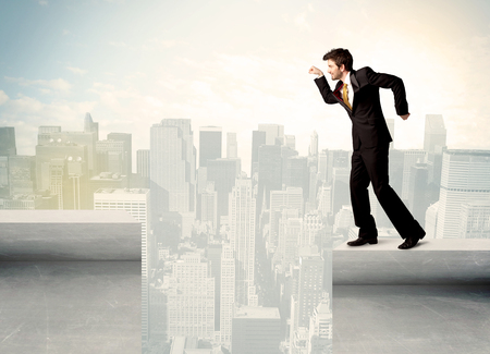bridging the gap: Businessman standing on the edge of rooftop with city background Stock Photo