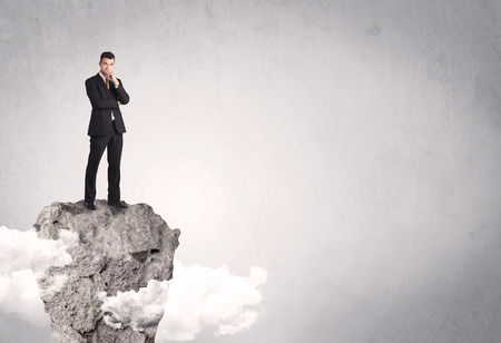 standing stone: A happy successful businessman standing on a stone cliff with clouds in front of clear empty grey background concept Stock Photo