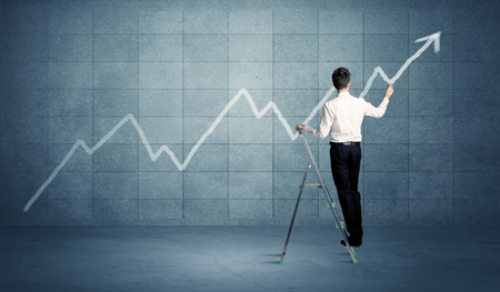 exponential: A man standing on a ladder and drawing a chart on blue wall background with exponential progressing curve, line