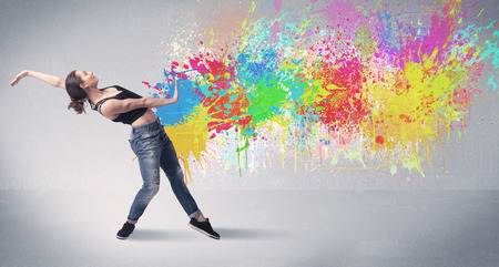 hip hop style: A funky contemporary hip hop dancer dancing in front of grey background with colorful bright paint splatter concept