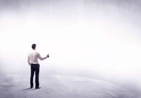Young sales businessman in elegant suit standing with his back in empty white space background concept Stock Photo