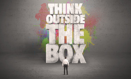 consider: Colorful wall with illustrated quote saying think outside the box for a small businessman standing in grey urban space concept Stock Photo