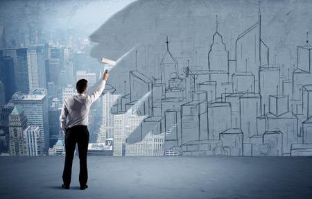 Un hombre de negocios en traje elegante con un rodillo de pintura en la mano y pintando el paisaje de la ciudad dibujada sobre el concepto de rascacielos urbanos