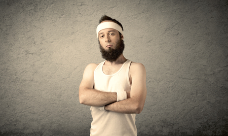 man health: A young man with beard, headstrap and glasses posing in front of blank grey wall background, imagining he has big muscles