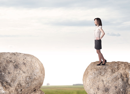 bridging: Young businesswoman standing on edge of rock mountain