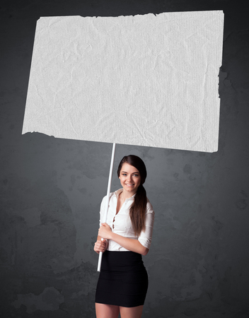 businesswoman suit: Young businesswoman holding a big blank booklet paper