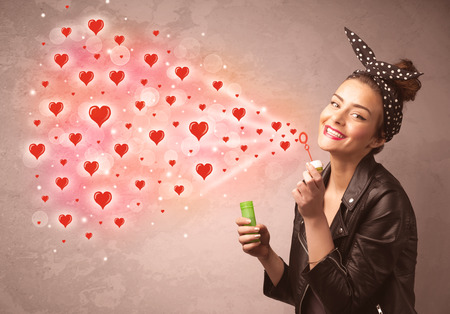 love blow: Pretty young girl blowing valentine red heart symbols