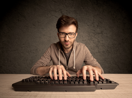 hacker: A young hacker with glasses dressed in casual clothes sitting at a desk and working on a computer keyboard in front of black clear concrete wall background concept Stock Photo