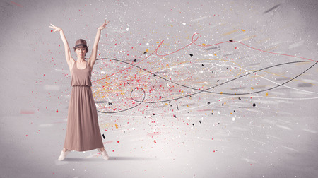 A young contemporary energetic dancer in action in front of a grey wall background with lines, spray dots and splatter concept Stock Photo