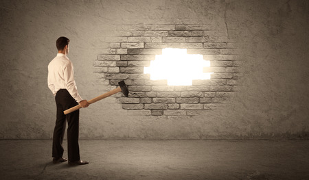 to break through: Business man hitting brick grungy wall with hammer and opening a hole Stock Photo