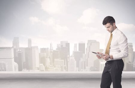 standing up: A young adult businessman standing in front of city landscape with skyscraper buildings and clouds concept