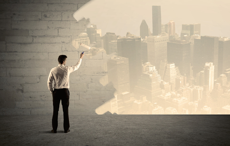 transforming: An elegant businessman with a paint roller transforming a brick wall into urban city landscape including tall buildings concept