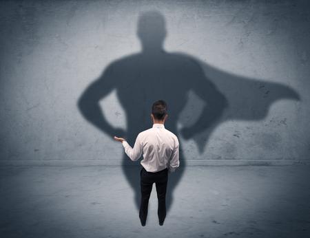 A magabiztos fiatal elegáns ügynök aktatáska szemben a falon, nézte szuper ember árnyéka koncepció