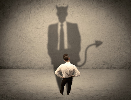 tricky: An experienced tricky businessman in suit looking at his devil desguise shadow reflected on the wall concept