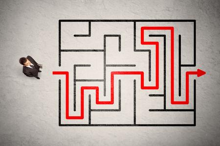 laberinto: empresario perdi� encontr� la manera en laberinto con flecha roja sobre fondo sucio Foto de archivo