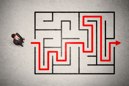 problem: Lost businessman found the way in maze with red arrow on grungy background