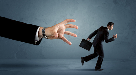 work worker: Business man running away from a huge hand concept on background