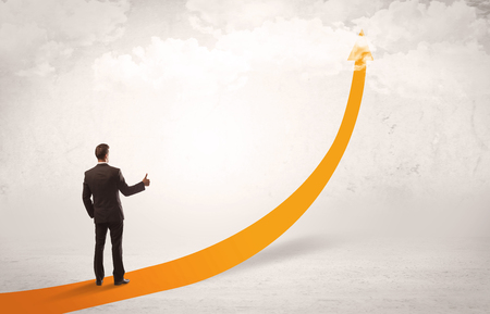 A young adult salesman standing on a big orange arrow pointing up in a bright empty space concept Foto de archivo