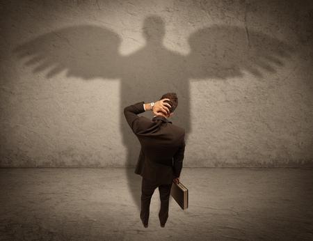 Un uomo d'affari di successo che tiene una cartella è dare pollici in su per il suo angelo ombra di fronte di un concetto di parete