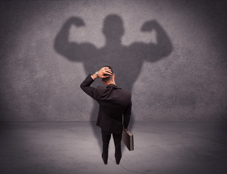 shadow man: A young salesman standing with his back, looking at his musculous shadow reflecting on the wall concept Stock Photo