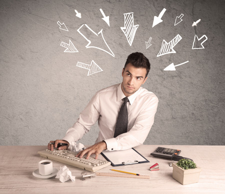 bad planning: A young businessman sitting at an office desk and working on paperwork with drawn arrows pointing at his head concept