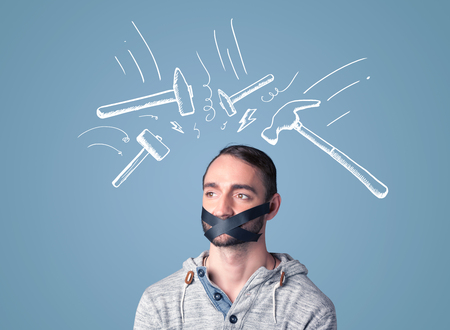 keep an eye on: Young man with taped mouth and white drawn beating hammer marks around his head Stock Photo
