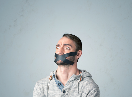 keep an eye on: Young man with taped mouth. Isolated on gray background