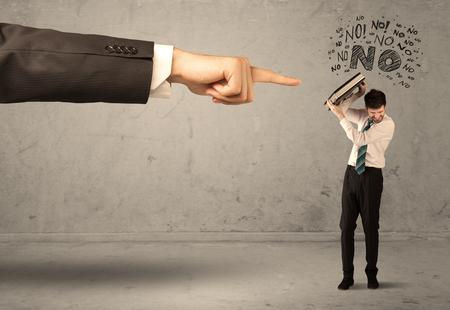 ashamed: Un joven empleado discrepar y discutir con el jefe, sintiendo concepto avergonzado. Una gran mano apuntando al empresario decir no
