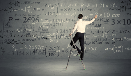 business change: A businessman in elegant suit standing on a small ladder and writing numbers, calculating on grey wall background