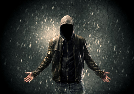shadow man: A faceless misterious man in hoodie and leather jacket standing in the dark with a visible silhouette concept