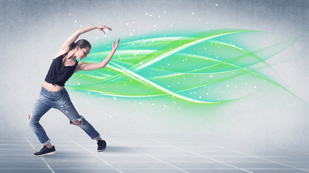 line dance: A good looking fresh street dancer dancing in front of grey background with white and bright, colorful green lines concept Stock Photo