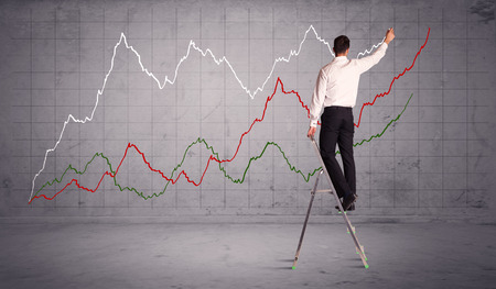 exponential: A guy in modern suit standing on a small ladder and drawing a chart on grey wall background with exponential progressing curves, lines