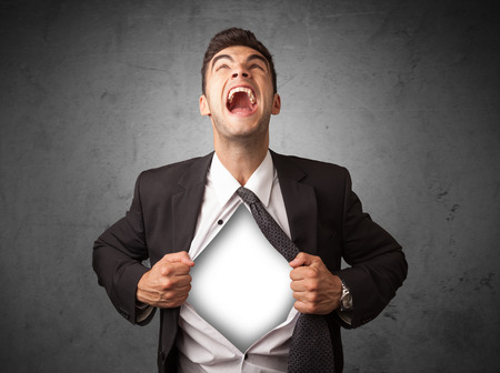 tearing: Businessman tearing off his shirt with white copyspace on chest on grungy background