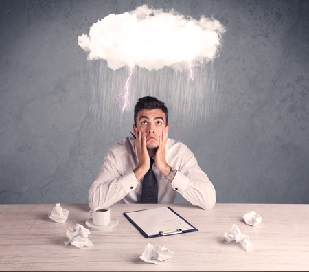 bad planning: An elegant office worker is having a bad day while working, illustrated by a white cloud above his head with heavy rain and thunder concept Stock Photo