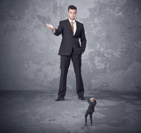 jefe enojado: Gran jefe enojado mirando pequeño concepto compañero de trabajo en el fondo