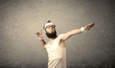 headstrap: A young man with beard, headstrap and glasses posing in front of blank grey wall background, imagining he has big muscles