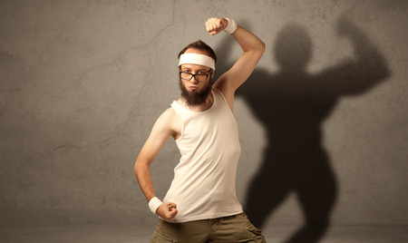 skinny: A funny young guy posing in front of brown background with musculous body shadow reflected on the wall Stock Photo