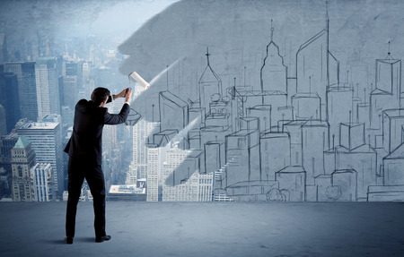 transforming: A businessman in elegant suit holding a paint roller in his hand and painting drawn city landscape over urban skyscrapers concept