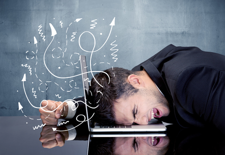 frustrated: A depressed businessman resting his head on a keyboard and shouting with illustration of ideas, arrows, lines leaving his head concept