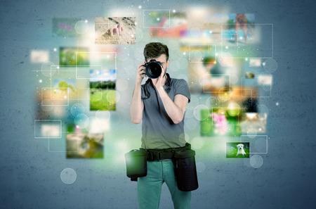 AFICIONADOS: Un joven aficionado a la fotografía con el equipo de cámara profesional que toma el cuadro en frente de la pared azul lleno de fotografías descoloridas y brillantes luces de concepto