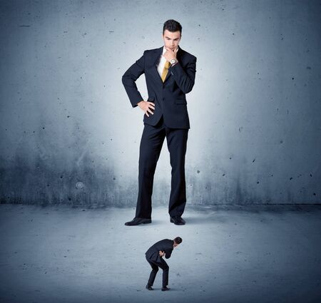 bad leadership: Angry huge business man lokking at small coworker guy concept on background Stock Photo