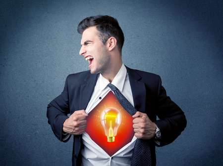 tearing: Businessman ripping off shirt and idea light bulb appears on his chest concept on backround