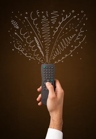 hand press: Hand holding a remote control, curly lines and arrows coming out of it Stock Photo