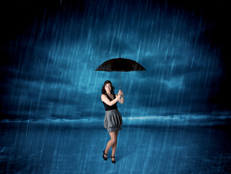Business woman standing in rain with an umbrella concept on background photo